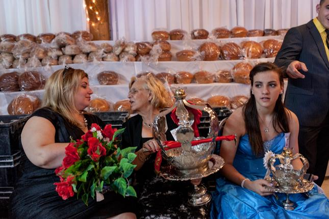 Three women in front of the bread given during the Feast.