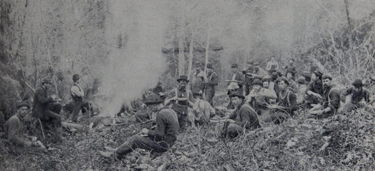 Photograph of loggers having lunch outdoor.