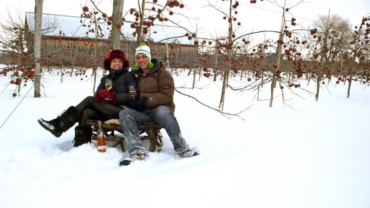 Two persons in front of a snowy orchard.