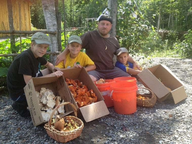 An adult and two children with their wild mushroom harvest.